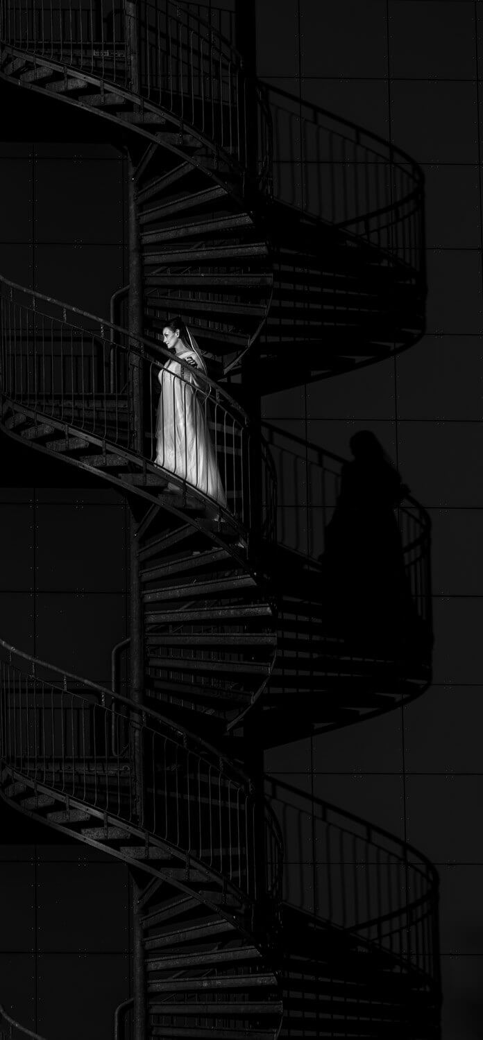 black & white photo of a bride going up a spiral staircase