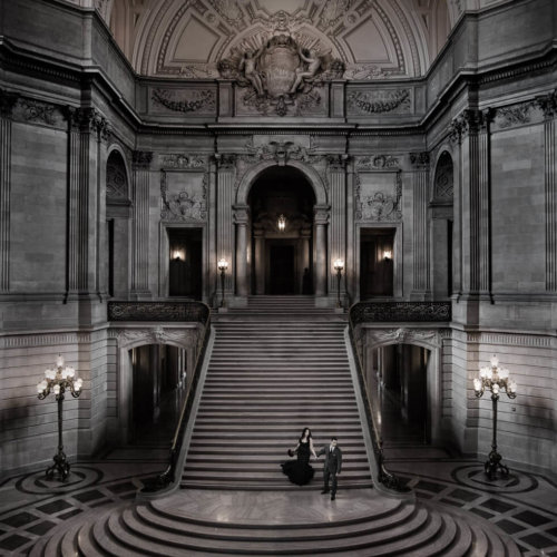 Bride & Groom walking down steps in a large building