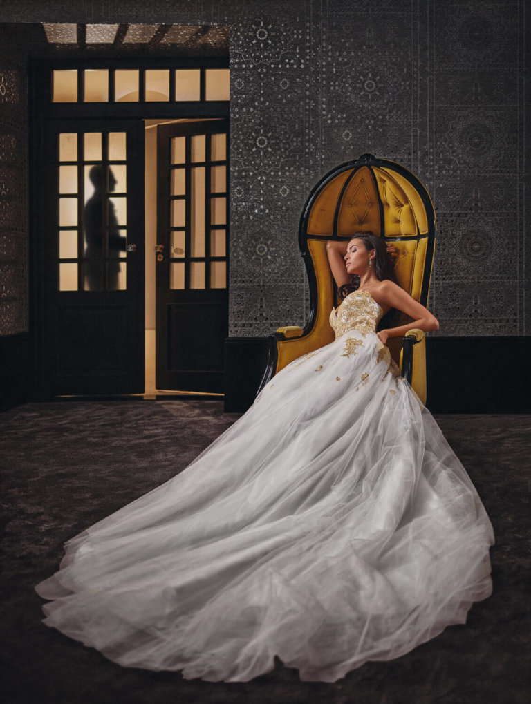 Silhouette of a groom coming into a room with a bride on a chair